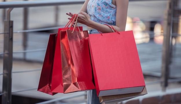 Jeune femme heureuse de style de vie tenant le sac à provisions avec profiter au centre commercial.