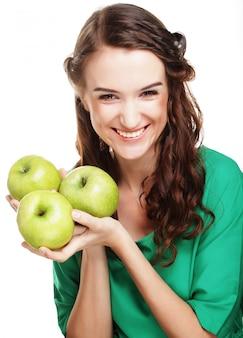 Jeune femme heureuse tenant des pommes vertes.