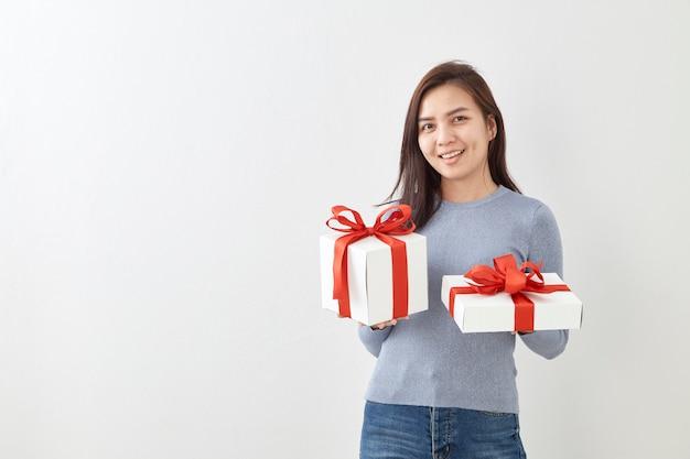 Jeune femme heureuse tenir sa boîte cadeau en mains