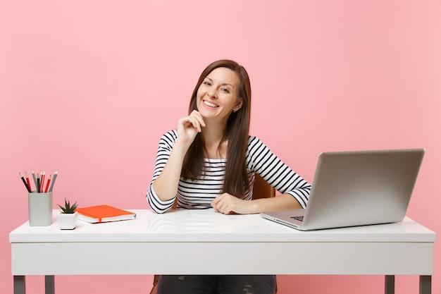 Jeune femme heureuse en vêtements décontractés, le menton appuyé sur la main, s'asseoir et travailler au bureau blanc avec un ordinateur portable contemporain
