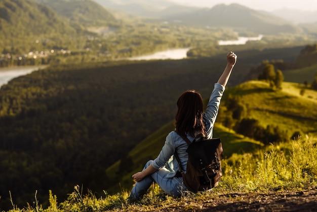 Jeune femme heureuse voyageur assis sur la montagne a levé la main vers le haut