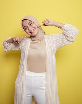 Jeune femme hijab sourit très heureux isolé sur un mur jaune