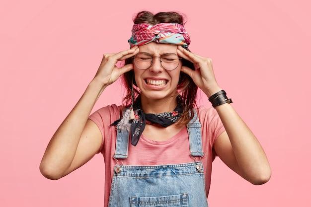 Une jeune femme hippie désespérée a de terribles maux de tête, serre les dents, a une expression triste, a des problèmes