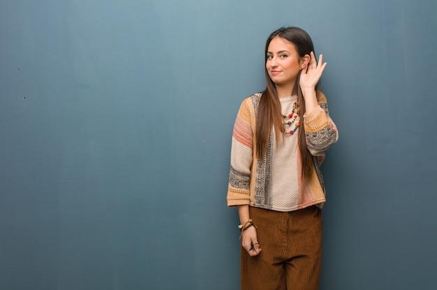 Jeune femme hippie essaie d'écouter un commérage