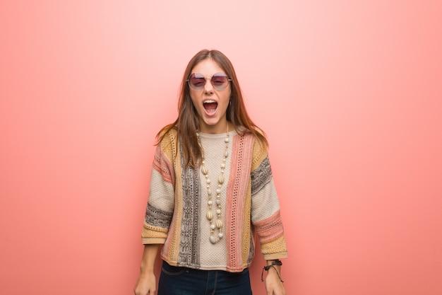 Jeune femme hippie sur fond rose criant très en colère et agressive