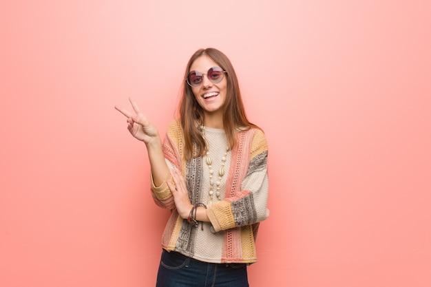 Jeune femme hippie sur fond rose faisant un geste de victoire