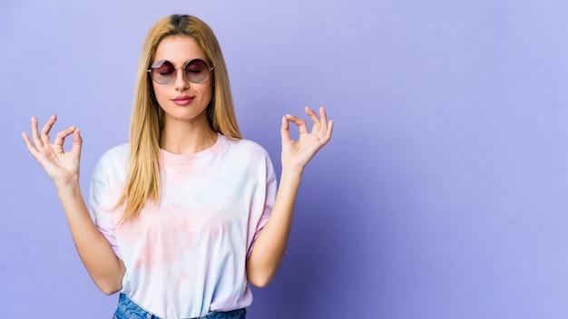 Jeune femme hippie avec des lunettes se détend, méditant