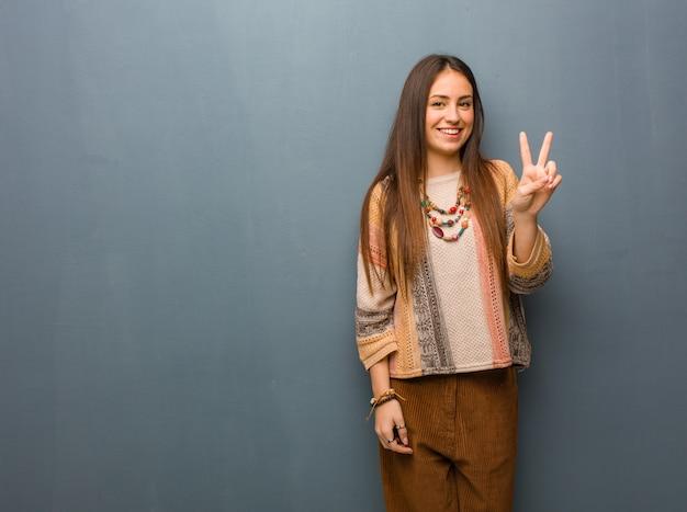 Jeune femme hippie montrant le numéro deux