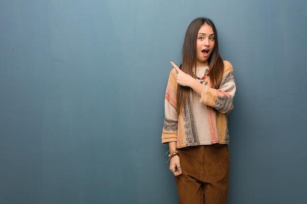Jeune femme hippie pointant sur le côté