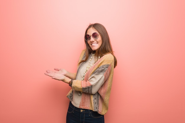 Jeune femme hippie sur rose tenant quelque chose avec les mains