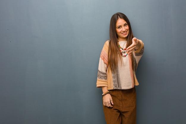 Jeune femme hippie tendre la main pour saluer quelqu'un