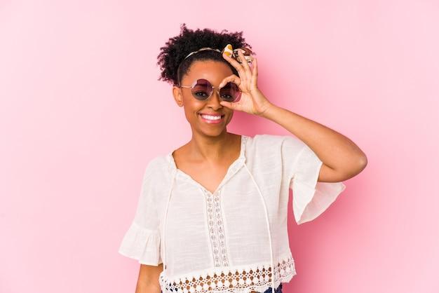 Jeune femme hipster afro-américaine isolée excitée en gardant le geste ok sur les yeux.