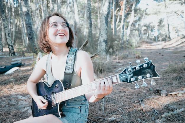 Jeune femme hipster assise dans un coffre jouant de la guitare sur fond de parc ou de jardin. adolescente apprenant à jouer des chansons et à écrire de la musique. hobby, mode de vie, détente, instrument, loisirs, concept d'éducation