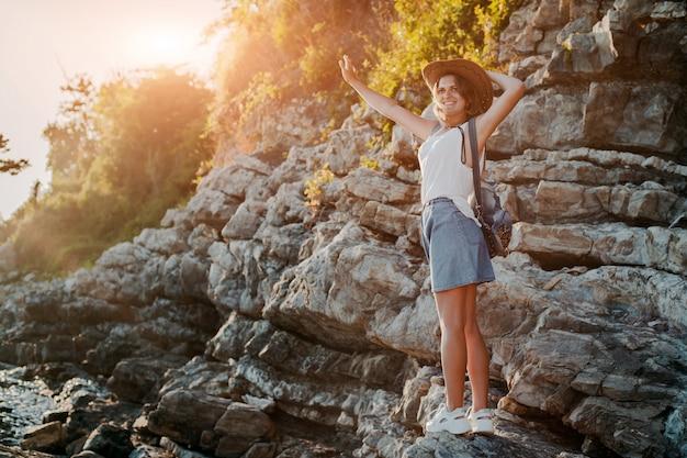 Une jeune femme hipster dans un chapeau et un rukzak avec ses mains, debout au sommet d'une falaise et regardant la mer au coucher du soleil.