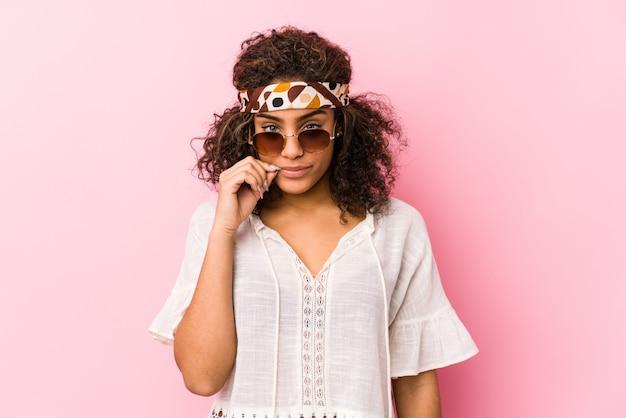 Jeune femme hipster isolée sur rose avec les doigts sur les lèvres gardant un secret.