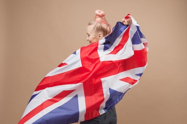 Jeune femme hipster de race blanche avec le drapeau de la grande-bretagne
