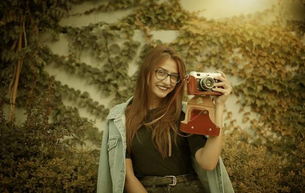 Jeune femme hipster en veste en jean et lunettes profite d'une caméra rétro film à l'extérieur