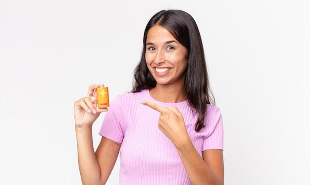 Jeune femme hispanique à l'air excité et surpris pointant sur le côté et tenant des piles