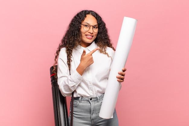 Jeune femme hispanique à l'air excitée et surprise pointant vers le côté et vers le haut pour copier l'espace. concept d'architecte
