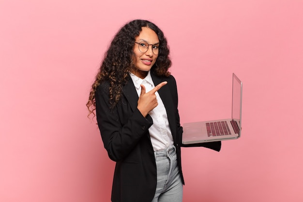 Jeune femme hispanique à l'air excitée et surprise pointant vers le côté et vers le haut pour copier l'espace