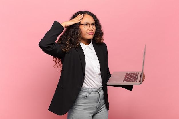 Jeune femme hispanique à l'air heureuse, étonnée et surprise, souriante et réalisant une bonne nouvelle incroyable et incroyable. concept d'ordinateur portable