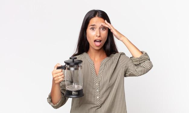 Jeune femme hispanique à l'air heureuse, étonnée et surprise et tenant une cafetière manuelle