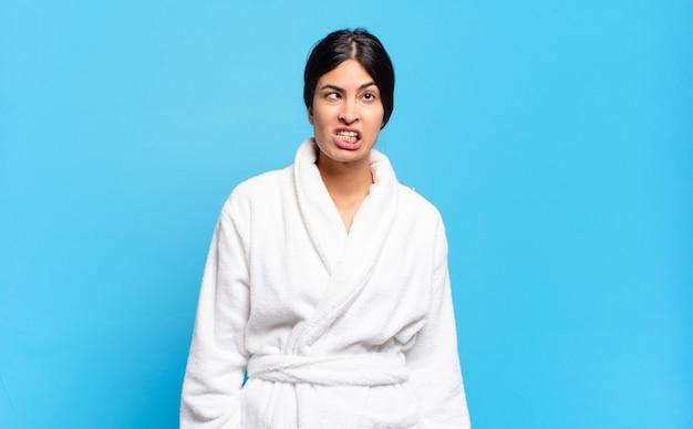 Jeune femme hispanique à l'air maladroit et drôle avec une expression stupide qui louche, plaisante et s'amuse. concept de peignoir