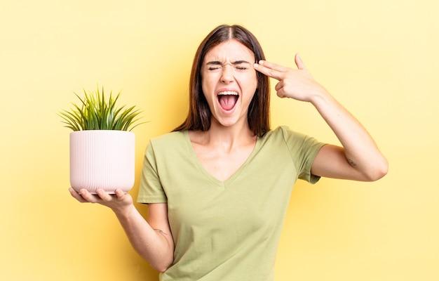 Jeune femme hispanique à l'air malheureuse et stressée, geste de suicide faisant signe d'arme à feu. concept de pot de plante