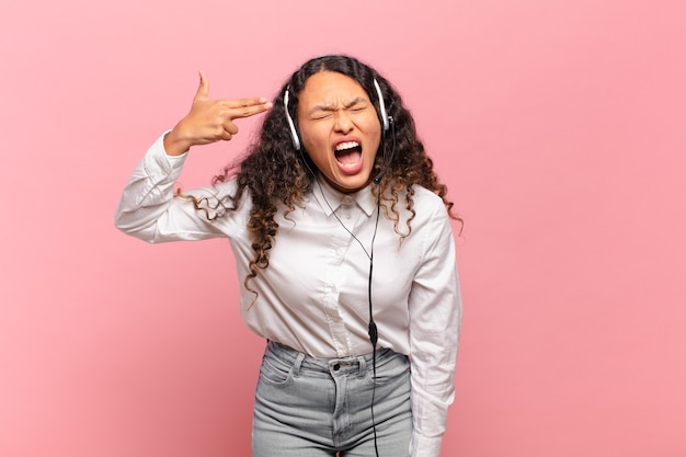 Jeune femme hispanique à l'air malheureuse et stressée, geste de suicide faisant un signe d'arme à feu avec la main, pointant vers la tête