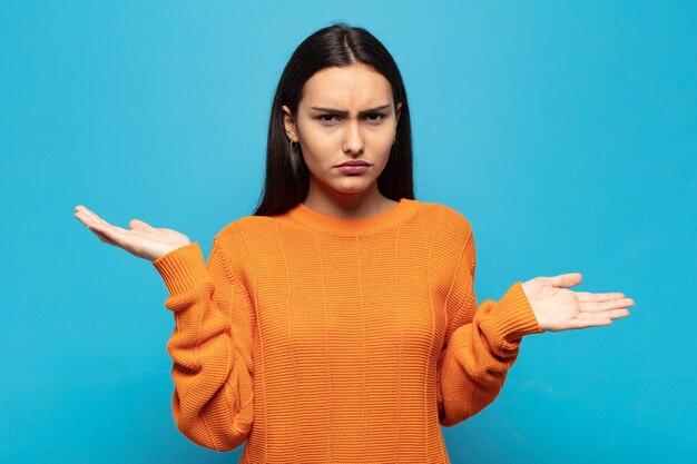 Jeune femme hispanique à l'air perplexe, confuse et stressée, se demandant entre différentes options, se sentant incertaine