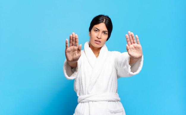 Jeune femme hispanique à l'air sérieuse, malheureuse, en colère et mécontente interdisant l'entrée ou disant stop avec les deux paumes ouvertes. concept de peignoir