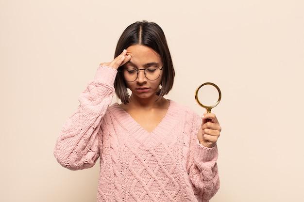 Jeune femme hispanique à l'air stressée et frustrée, travaillant sous pression avec un mal de tête et troublée par des problèmes