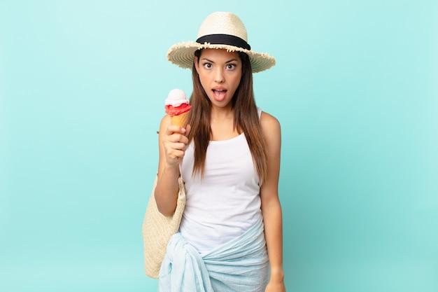 Jeune femme hispanique à l'air très choquée ou surprise et tenant une glace. concept d'été