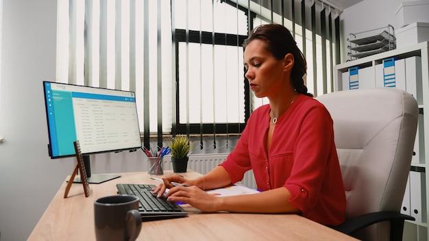 Jeune femme hispanique assise au bureau et travaillant sur un ordinateur de bureau. entrepreneur assis devant l'ordinateur dans l'espace de travail d'une entreprise professionnelle en tapant sur le clavier en regardant le moniteur rédiger des rapports