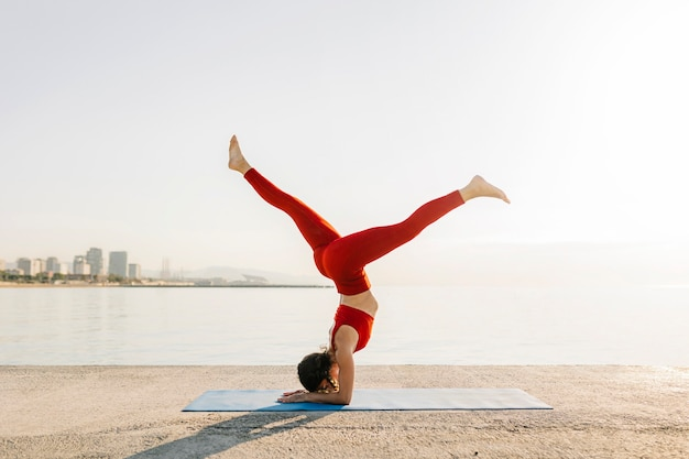 Jeune femme hispanique athlétique en vêtements de sport rouges faisant du yoga le matin au bord de la mer - position utthita pada sirsana - concept de mode de vie bien-être et soins de santé