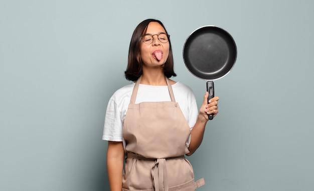 Jeune femme hispanique avec une attitude joyeuse, insouciante et rebelle, plaisantant et sortant la langue, s'amusant