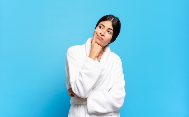 Jeune femme hispanique au regard concentré, se demandant avec une expression douteuse, levant les yeux et sur le côté
