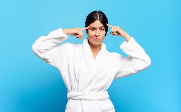 Jeune femme hispanique au regard sérieux et concentré, faisant un remue-méninges et réfléchissant à un problème difficile. concept de peignoir