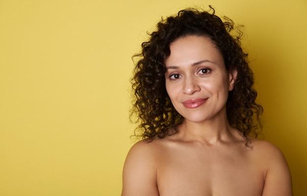 Jeune femme hispanique aux cheveux bouclés mignon souriant à la caméra en se tenant debout sur le jaune avec espace de copie.