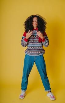 Jeune femme hispanique aux cheveux bouclés portant un sweat à capuche et un jean sur jaune