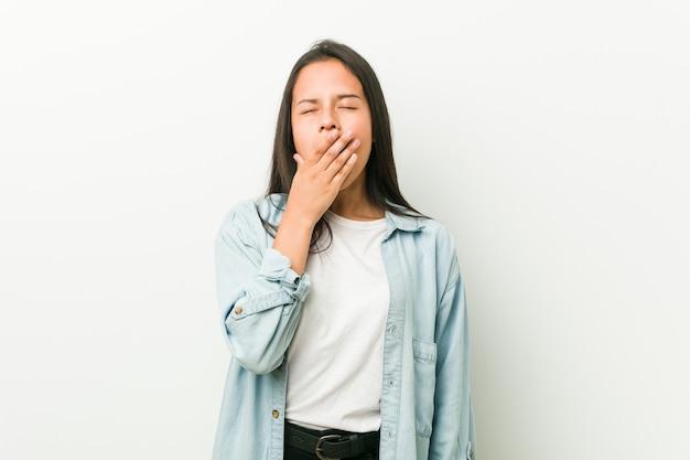 Jeune femme hispanique bâillant montrant un geste fatigué qui couvre la bouche avec la main.