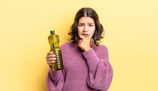 Jeune femme hispanique avec la bouche et les yeux grands ouverts et la main sur le menton. concept d'huile d'olive