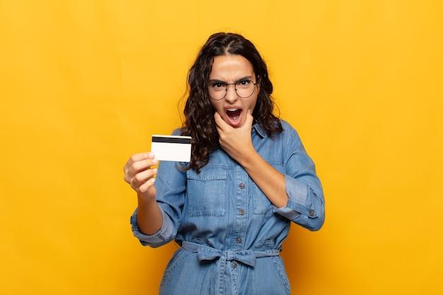 Jeune femme hispanique avec la bouche et les yeux grands ouverts et la main sur le menton, se sentant désagréablement choqué, disant quoi ou wow