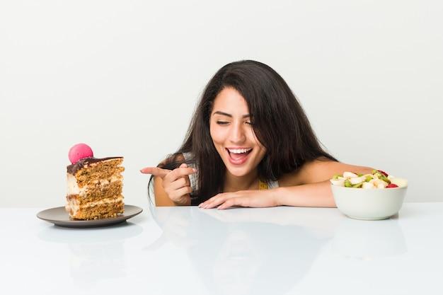 Jeune femme hispanique choisissant entre un gâteau ou un bol de fruits