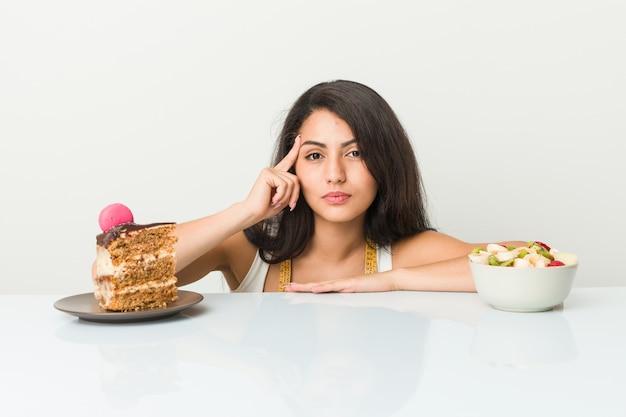 Jeune femme hispanique choisissant entre un gâteau ou un fruit pointant sa tempe avec le doigt, pensant, concentrée sur une tâche.