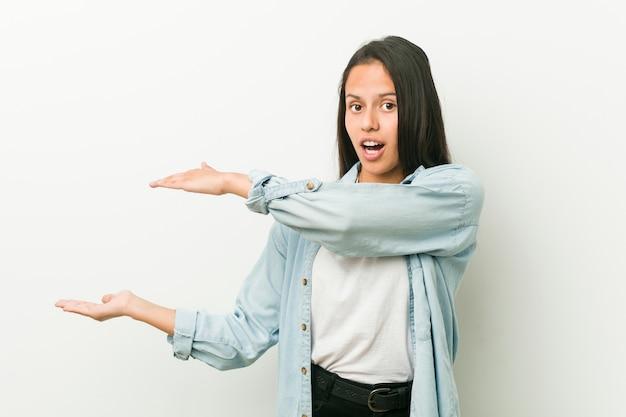 Jeune femme hispanique choquée et émerveillée tenant un entre ses mains.