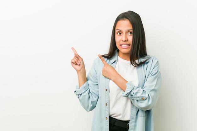 Jeune femme hispanique choquée pointant avec des index vers un espace de copie.