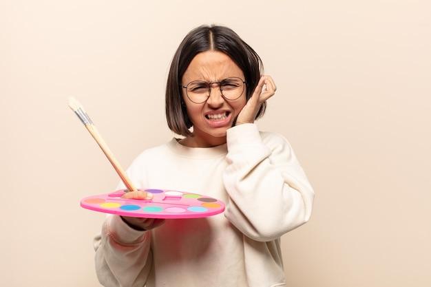 Jeune femme hispanique à la colère, stressée et agacée, couvrant les deux oreilles à un bruit assourdissant, un son ou une musique forte