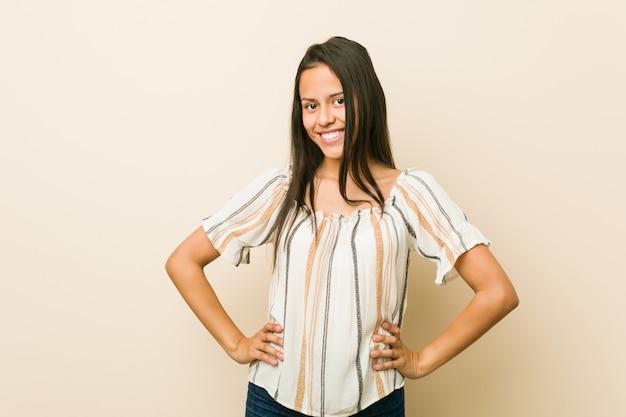 Jeune femme hispanique confiante en gardant les mains sur les hanches.
