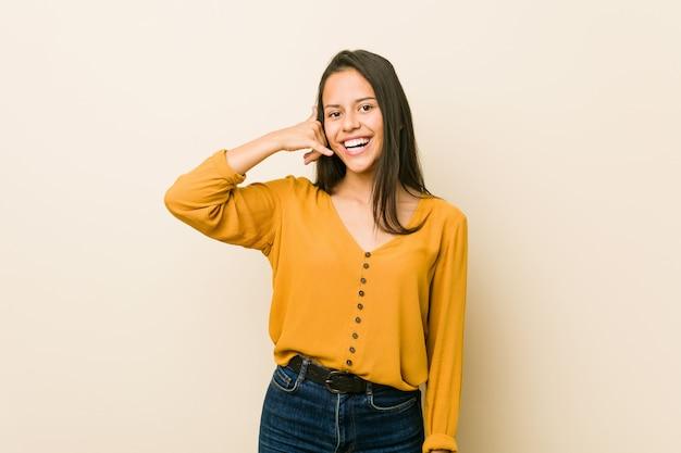 Jeune femme hispanique contre un mur beige, montrant un geste d'appel avec les doigts.